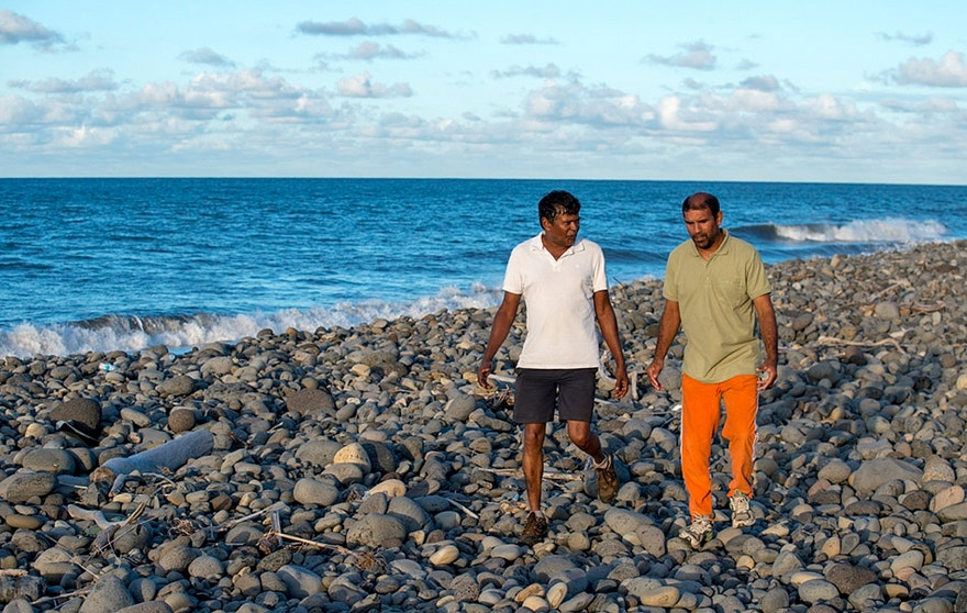 July 30, 2015 - Johnny Begue (R), who found plane debris Wednesday on this beach in Saint-Andre, on the French Indian Ocean island of La Reunion, walks with his friend Andre Tevane. Begue found a flaperon, which help pilots control an aircraft in flight, on Wednesday.  French authorities are studying the piece to determine whether it came from Malaysia Airlines Flight MH370.