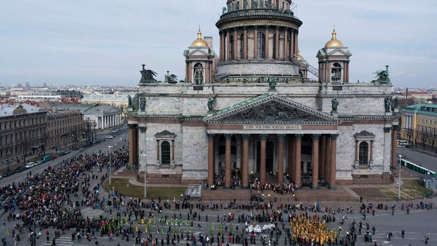 FILE - In this file aerial photo taken on Sunday, April  13, 2014, Orthodox priests and believers participate in the Palm Sunday procession around the St. Isaak's Cathedral in St. Petersburg, Russia. The Russian Orthodox Church on Friday defended its controversial bid to fully take over St. Petersburg's landmark St. Isaac's Cathedral, saying it's in line with the law and wouldn't hamper tourist access. (AP Photo/Dmitry Lovetsky, file)