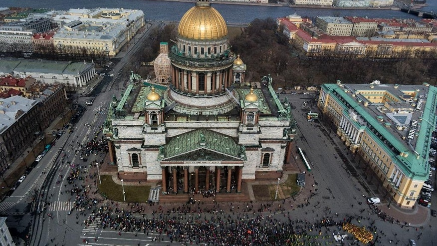 FILE - In this file aerial photo taken on Sunday, April  13, 2014 , Orthodox priests and believers participate in the Palm Sunday procession around the St. Isaak's Cathedral in St. Petersburg, Russia. The Russian Orthodox Church on Friday, July 31, 2015 defended its controversial bid to fully take over St. Petersburg's landmark St. Isaac's Cathedral, saying it's in line with the law and wouldn't hamper tourist access. (AP Photo/Dmitry Lovetsky, file)