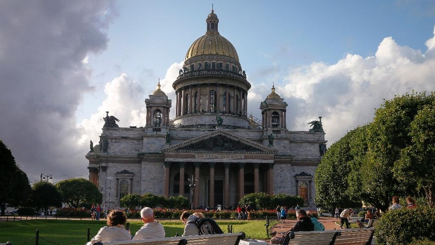 People rest in a park in front of the St. Isaac's Cathedral in St.Petersburg, Russia, Friday, July 31, 2015. The Russian Orthodox Church on Friday defended its controversial bid to fully take over St. Petersburg's landmark St. Isaac's Cathedral, saying it's in line with the law and wouldn't hamper tourist access. (AP Photo/Dmitry Lovetsky)