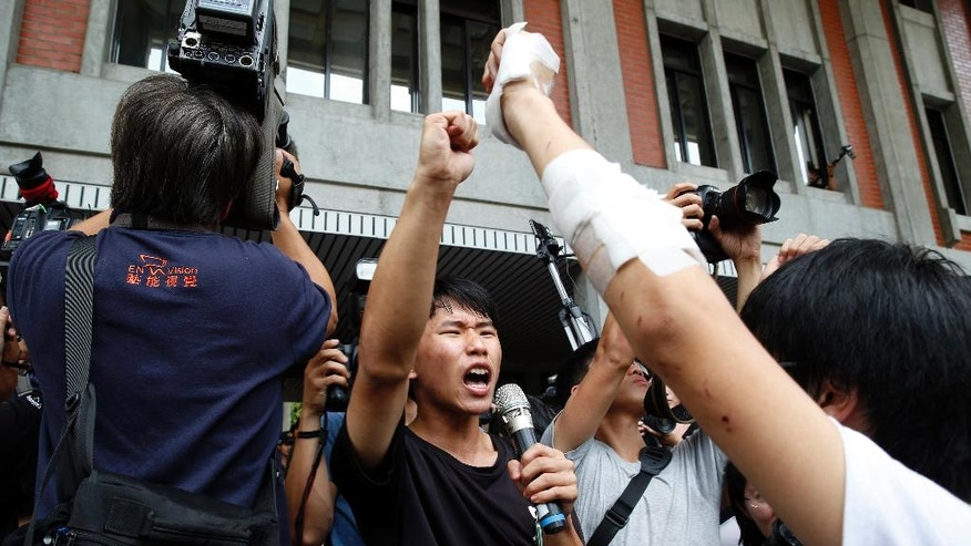 Student protesters against changes to their curriculum shout slogans as they occupy the area inside the gates of the Ministry of Education in Taipei, Taiwan, Friday, July 31, 2015. Dozens of students have staged a sit-in at Taiwan's Education Ministry demanding that officials take responsibility for a student leader who killed himself in an apparent protest over curriculum changes that critics say overemphasize China's ties to the island. (AP Photo/Wally Santana)