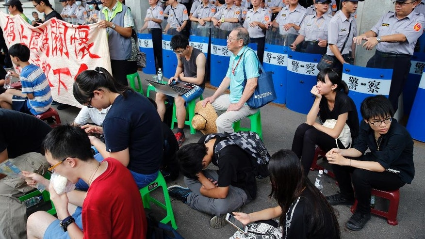 Student protesters against changes to their curriculum occupy the area inside the gates of the Ministry of Education in Taipei, Taiwan, Friday, July 31, 2015. Dozens of students have staged a sit-in at Taiwan's Education Ministry demanding that officials take responsibility for a student leader who killed himself in an apparent protest over curriculum changes that critics say overemphasize China's ties to the island. (AP Photo/Wally Santana)