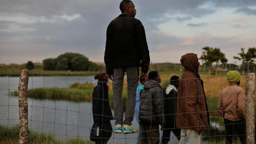 Migrants stand along a road leading to the Channel Tunnel, in Calais, northern France, Thursday, July 30, 2015. Undeterred by an influx of French riot police, a surveillance helicopter, or a ninth death this summer among the tens of thousands who attempt to cross the Channel, the migrants came in groups of a dozen or more. Men and women, some hiding their faces beneath bandannas, walked single file to sneak over a bent fence along the train tracks leading to the tunnel and ultimately to England. (AP Photo/Thibault Camus)