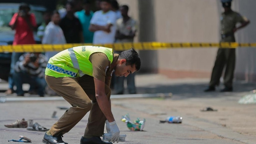 A Sri Lankan police officer inspects the site of an attack in Colombo, Sri Lanka, Friday, July 31, 2015. Unidentified gunmen opened fire at campaign workers in Sri Lanka's capital on Friday in the first major political violence before the parliamentary elections scheduled on Aug. 17. (AP Photo/Eranga Jayawardena)