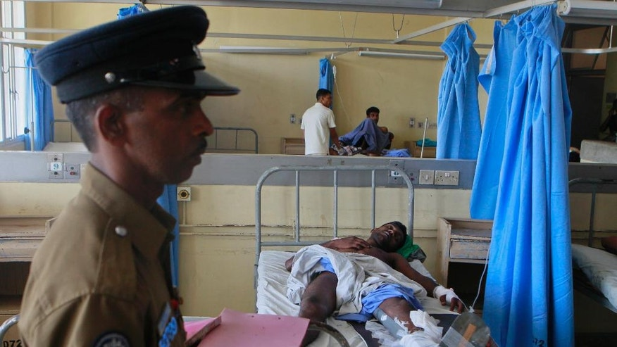 A Sri Lankan police officer stands guard near a victim injured in an attack, at a hospital in Colombo in Colombo, Sri Lanka, Friday, July 31, 2015. Unidentified gunmen opened fire at campaign workers in Sri Lanka's capital on Friday in the first major political violence before the parliamentary elections scheduled on Aug. 17. (AP Photo/Eranga Jayawardena)
