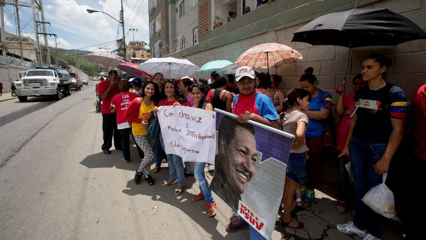Government supporters, one holding a poster of Venezuela's late President Hugo Chavez, protest outside a distribution center belonging to Venezuela's largest food company, Empresas Polar, in La Yaguara neighborhood, in Caracas, Venezuela, Friday, July 31, 2015. The protesters are asking that the company give up their land so they can build homes of their own on the Empresas Polar property. Soldiers took over the warehouse complex used by Empresas Polar late Wednesday just as Venezuela's federation of brewers announced that Polar's beer manufacturing subsidiary is shutting two of its six plants because of a lack of imported barley.  (AP Photo/Fernando Llano)