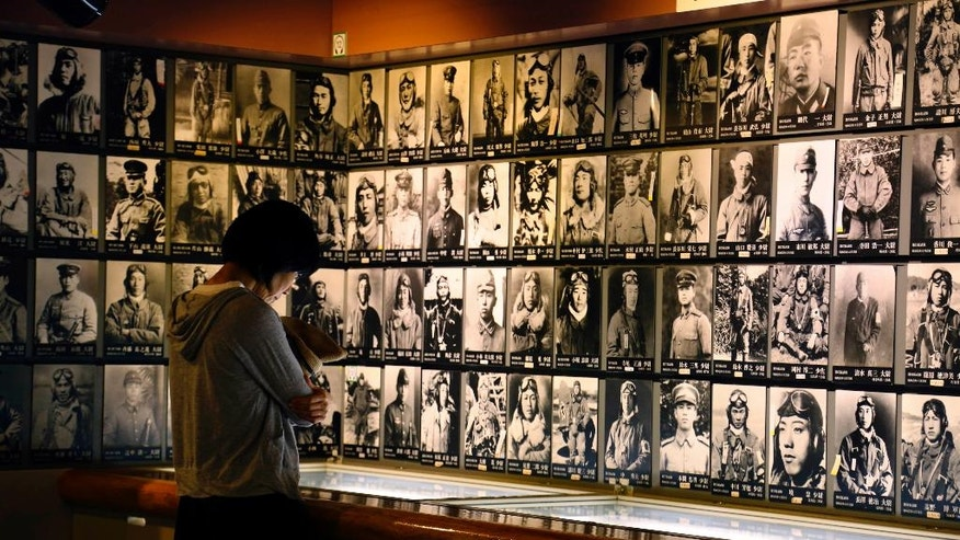 In this July 17, 2015 photo, a visitor looks at photos of deceased pilots of the Imperial Japanese Army in the World War II at Chiran Peace Museum in Chiran in Kagoshima Prefecture, south west of Japan. As young army pilots took off on suicide-attack missions in the closing days of World War II, the schoolgirls in this southwestern Japanese town waved handkerchiefs and branches of pink blossoms. Chiran served as the takeoff spot for 439 pilots on suicide-attack missions, many of them also teenagers. Japan surrendered four months later. (AP Photo/Yuri Kageyama)