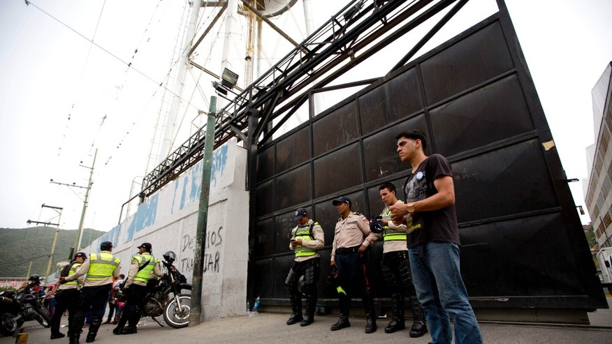 Bolivarian Police officers at the gate of distribution center  of Empresas Polar, in Caracas, Venezuela, Thursday, July 30, 2015.