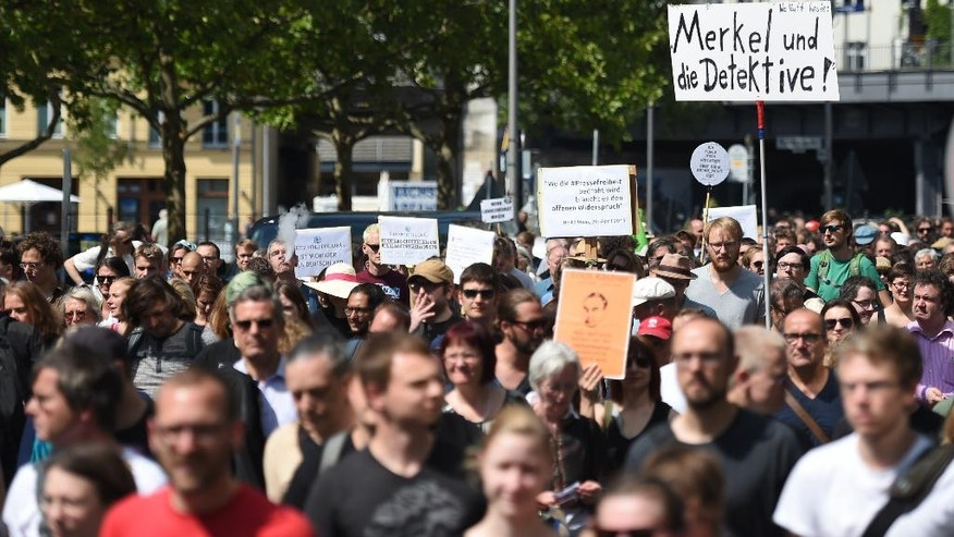 "Participants of a  demonstration  protest in Berlin, Saturday Aug. 1, 2015.  Banner at right reads  ""Merkel und die Detektive!"" (lt: Merkel and the detectives). Some 1,300 people rallied in Berlin for the freedom of the press in support of two journalists who prosecutors are investigating for treason over two reports revealing authorities' plans to expand surveillance of online communication. Website Netzpolitik.org, which covers digital rights issues, said Thursday it was notified by federal prosecutors of the probe against its staff and an unidentified source over the two reports.   (Britta Pedersen/dpa via AP)"