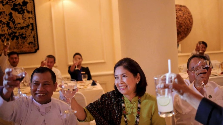 In this August 6, 2013, photo, Aye Aye Win, center, The Associated Press chief of bureau for Myanmar, is seated with unidentified guests as glasses are raised during a toast during a dinner in Yangon, Myanmar.  After 25 years with AP, Aye Aye Win, 61, is retiring after a career that followed the legacy left by her father, U Sein Win, AP's Myanmar correspondent from 1969-1989, who was jailed three times while fighting for press freedom. (AP Photo/Wong Maye-E)