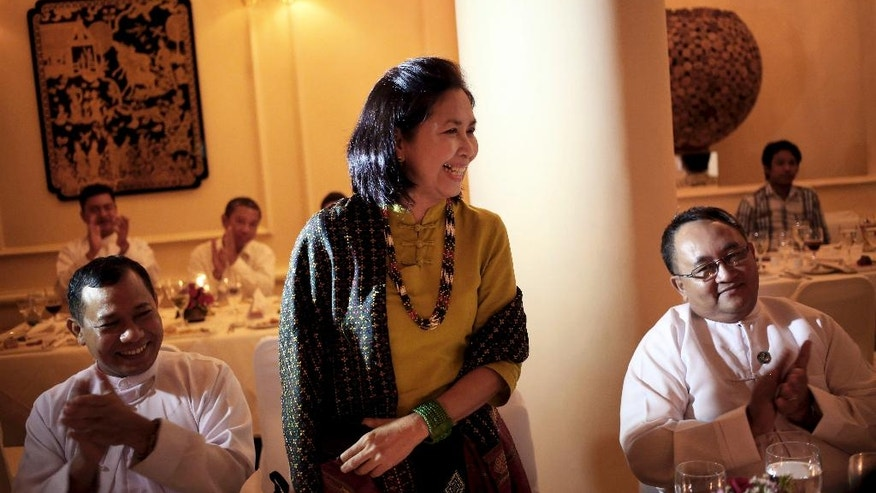 In this August 6, 2013, photo, Aye Aye Win, center, The Associated Press chief of bureau for Myanmar, stands to applause as she is acknowledged for her work at a dinner in Yangon, Myanmar.  After 25 years with AP, Aye Aye Win, 61, is retiring after a career that followed the legacy left by her father, U Sein Win, AP's Myanmar correspondent from 1969-1989, who was jailed three times while fighting for press freedom. (AP Photo/Wong Maye-E)