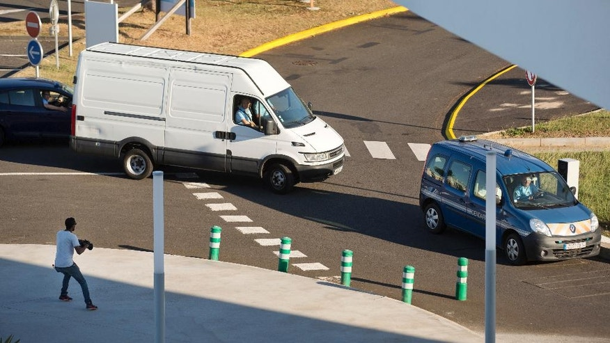 A white van carrying a wooden box containing the wing part that was washed up on a beach, is filmed by a television cameraman as it receives a vehicle escort by the French gendarmerie while driving to a cargo hangar at the Roland Garros Airport in Sainte-Marie, on the north coast of the Indian Ocean island of Reunion Friday, July 31, 2015.  Investigators prepared to load a sea-encrusted wing fragment onto a plane bound for France on Friday, to undergo further investigations to learn whether the aircraft remnant could help unlock the mystery of missing Malaysia Airlines Flight 370. (AP Photo/Ben Curtis)