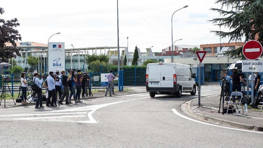 CORRECTS LOCATION  Members of the media watch as a white van, accompanied by police motorcycles and a police car transporting what is believed to be debris from a Boeing 777 plane that washed up on an Indian Ocean island, arrives at Direction Generale de L'armement (DGA) facilities in Balma, near Toulouse, south-western France, Saturday, Aug. 1, 2015. A piece of plane wing that could be from missing Malaysia Airlines Flight 370 arrived Saturday in Toulouse, France, for inspection by military aviation experts.The 6-foot-long part, wrapped in a box and shipped as cargo, was flown from the small island of Reunion, near Madagascar. (AP Photo/Fred Lancelot)