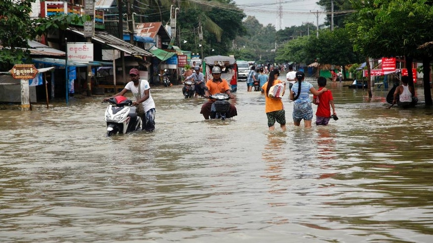 Local residents wade through a flooded road in Bago, 80 kilometers (50 miles) northeast of Yangon, Myanmar, Saturday, Aug 1, 2015. Myanmar's president has declared several regions of the country to be disaster zones, as forecasts of heavy rain for the next few days have heightened fears that already dire flooding in many parts of the country will get worse. (AP Photo/Khin Maung Win)