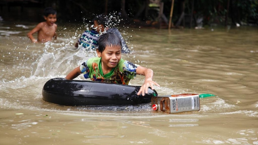A boy rides inner tube as he swims in a flooded road in Bago, 80 kilometers (50 miles) northeast of Yangon, Myanmar, Saturday, Aug 1, 2015. Myanmar's president has declared several regions of the country to be disaster zones, as forecasts of heavy rain for the next few days have heightened fears that already dire flooding in many parts of the country will get worse. (AP Photo/Khin Maung Win)