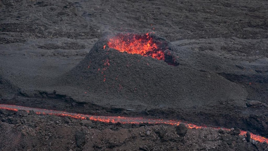 "Lava erupts from the Piton de la Fournaise ""Peak of the Furnace"" volcano, on the southeastern corner of the Indian Ocean island of Reunion Saturday, Aug. 1, 2015. Spewing red-hot lava, one of the most active volcanoes in the world is currently erupting on this Indian Ocean island, where the world's attention has been focused since a wing fragment believed to be from the missing Malaysian jet was discovered washed up on a beach. (AP Photo/Ben Curtis)"