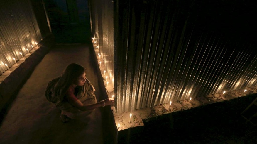 In this Friday, July 31, 2015 photo, a woman lights candles in celebration at Dashiarchhara, in Kurigram enclaves, Bangladesh. At the stroke of midnight Friday, tens of thousands of stateless people who were stranded for decades along the poorly defined border between India and Bangladesh will finally get to choose their citizenship, as the two countries swapped more than 150 pockets of land to settle the demarcation line dividing them. (AP Photo)