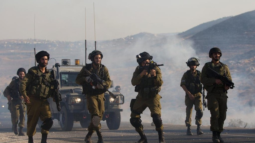 Israeli soldiers clash with Palestinians at the entrance of Duma village near the West Bank city of Nablus, Saturday, Aug. 1, 2015. Tensions remain high after suspected Jewish assailants set fire to a West Bank home and burned a sleeping Palestinian toddler to death. The child's 4-year-old brother and both his parents were also seriously wounded. The attack drew Palestinian anger and widespread Israeli condemnation. (AP Photo/Majdi Mohammed)