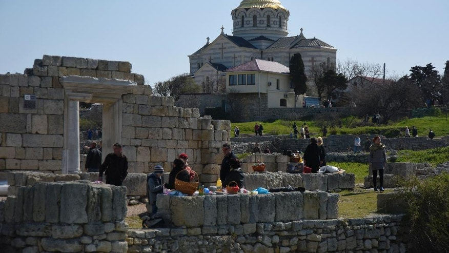 In this photo taken on Sunday, April  12, 2015, people gather at the area that was the ancient Greek colony of Chersonesus, and with the St. Vladimir's Cathedral in the background, just outside Sevastopol, the main port city in Crimea, the Black Sea Peninsula annexed by Russia from Ukraine last year. Russia's President Vladimir Putin has placed this major archaeological site in Crimea under federal control following turmoil over the appointment of its director. (AP Photo/Alexander Polegenko)