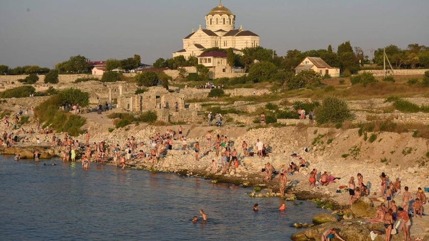 In this photo taken on Saturday, July  25, 2015, people gather at the beach area of the Black Sea, near to the area that was the ancient Greek colony of Chersonesus, and with the St. Vladimir's Cathedral in the background, just outside Sevastopol, the main port city in Crimea, the Black Sea Peninsula annexed by Russia from Ukraine last year. Russia's President Vladimir Putin has placed this major archaeological site in Crimea under federal control following turmoil over the appointment of its director. (AP Photo/Alexander Polegenko)