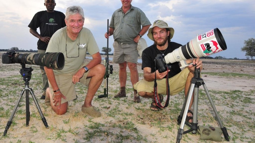 In this photo taken Nov. 9,  2014 photographer Brent Stapelkamp, front right,  with colleagues in the Hwange National Park, Zimbabwe. Stapelkamp, a lion researcher and part of a team that had tracked and studied Cecil the lion for nine years darted him and attached a collar last year. He was probably the last person to get up close before Minnesota dentist Walter Palmer killed the now-famous lion with the bushy black mane and, aided by a Zimbabwean professional hunter, cut off its head and skin for trophies.  (AP Photo/Derek Whalley)
