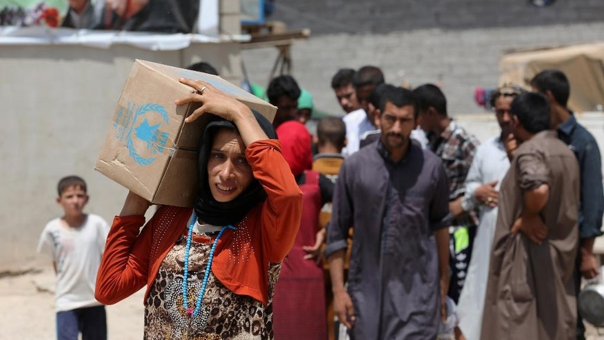 A woman carries a box of food from the World Food Programme at al-Takia refugee camp in Baghdad, Iraq, Thursday, July 30, 2015. The number of people displaced within Iraq due to violence and fighting by the Islamic State group has exceeded 3 million, the United Nations said in June. (AP Photo/Khalid Mohammed)
