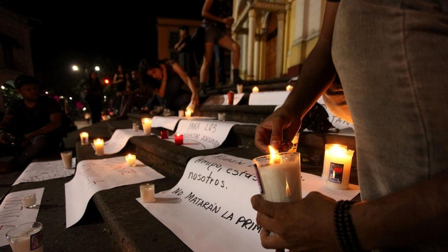 Journalists hold a late night vigil to protest against the latest murder of a fellow journalist in Veracruz, Mexico, Saturday Aug. 1, 2015. A photographer for the Mexican investigative magazine Proceso, who had fled his home state after being harassed, was among five people found slain early Saturday in an apartment in Mexico City, according to the magazine. The body of Ruben Espinosa, who collaborated with Proceso and other media, was identified by a family member at the morgue Saturday afternoon, Proceso reported, adding that he had two gunshot wounds. (AP Photo/Felix Marquez)