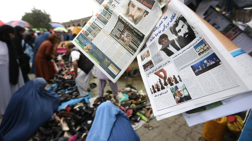 Newspapers hang for sale at a stand  carrying headlines about the new leader of the Afghan Taliban, Mullah Akhtar Mohammad Mansoor, in Kabul, Afghanistan, Saturday, Aug. 1, 2015. The new leader of the Afghan Taliban vowed to continue his group's bloody, nearly 14-year insurgency in an audio message released Saturday, urging his fighters to remain unified after the death of their longtime leader. (AP Photo/Rahmat Gul)
