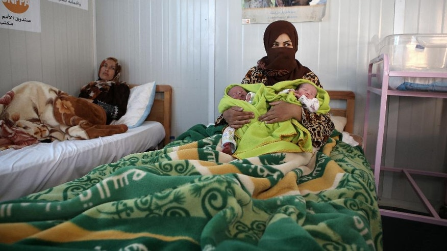 In this Wednesday, July 29, 2015 photo, Syrian refugee Maan Turkman, 31, holds her twin infants Mohammed, left, and Ahmed, at a maternity clinic in Zaatari refugee camp, in Mafraq, Jordan. On Zaatari's anniversary this past week, the transformation from tent camp to city symbolizes the failure of rival world powers to negotiate an end Syria's war. But some say it's also a reminder that the shift from emergency aid to long-term solutions, such as setting up a water network to replace expensive delivery by truck, should have come much sooner. (AP Photo/Raad Adayleh)