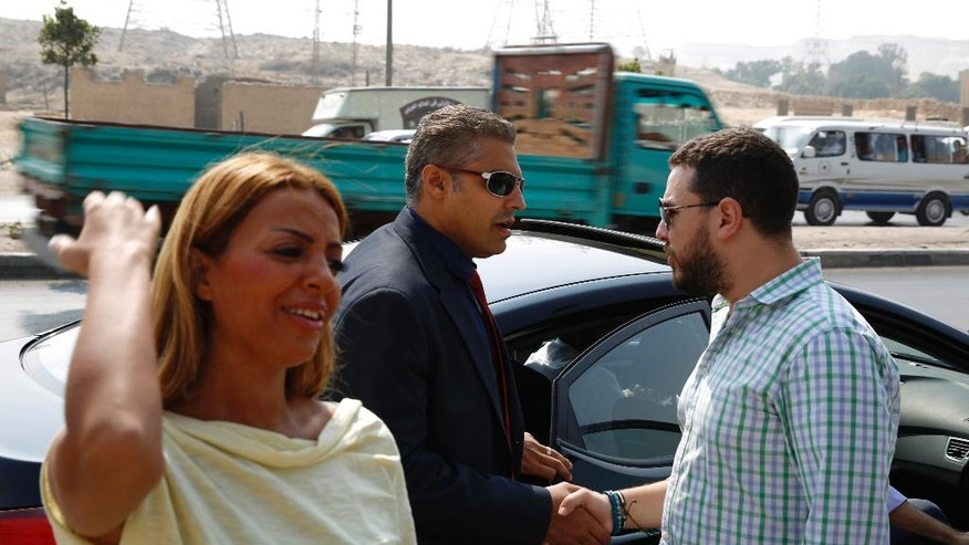 Canadian Al-Jazeera English journalist Mohammed Fahmy, center, and his fiance Marwa Omara, left, arrive to Tora prison, in Cairo, Egypt, Sunday, Aug. 2, 2015. An Egyptian court on Sunday again postponed announcing a verdict in the retrial of three Al-Jazeera English journalists, extending the long-running trial criticized worldwide by press freedom advocates and human rights activists. (AP Photo/Hassan Ammar)