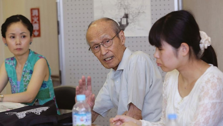 In this Saturday, July 25, 2015 photo, Shigeyuki Katsura, center, 84-year-old survivor of the Nagasaki atomic bombing, speaks his experience 70 years ago, in the western Tokyo suburb of Kunitachi. In a government-organized program, 20 trainees ranging from their 20s to their 70s are studying wartime history, taking public speech lessons from a TV anchor and hearing stories from Katsura and another Kunitachi resident who survived Hiroshima. (AP Photo/Koji Sasahara)