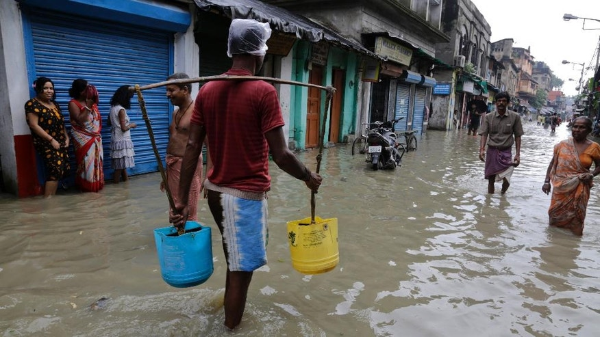 A drinking water vendor makes his way through a flooded street in Kolkata, India, Sunday, Aug. 2, 2015. Parts of the city were flooded Sunday after water from the Ganges river rose following monsoon rains. (AP Photo/ Bikas Das)