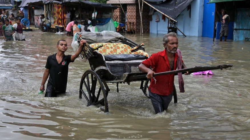 An Indian hand rickshaw puller makes his way through a flooded street in Kolkata, India, Sunday, Aug. 2, 2015. Parts of the city were flooded Sunday after water from the Ganges river rose following monsoon rains. (AP Photo/ Bikas Das)