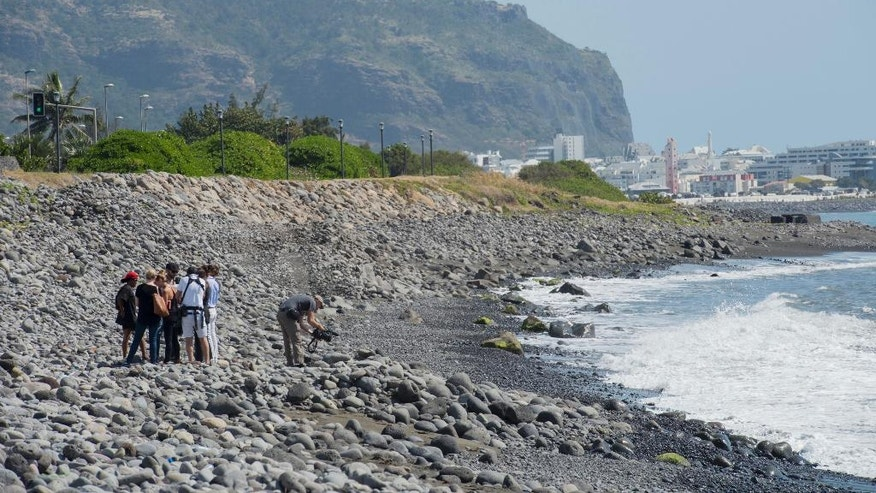 Workers for an association responsible for maintaining paths to Jamaica beach from being overgrown by shrubs, search the beach for possible additional airplane debris near the shore where an airplane wing part was washed up, in the early morning near to Saint-Denis  on the north coast of the Indian Ocean island of Reunion Sunday, Aug. 2, 2015. A barnacle-encrusted wing part that washed up on the remote Indian Ocean island earlier could help solve one of aviation's greatest mysteries, as investigators work to connect it to the Malaysia Airlines Flight 370 that vanished more than a year ago with 293 people aboard. (AP Photo/Fabrice Wislez)