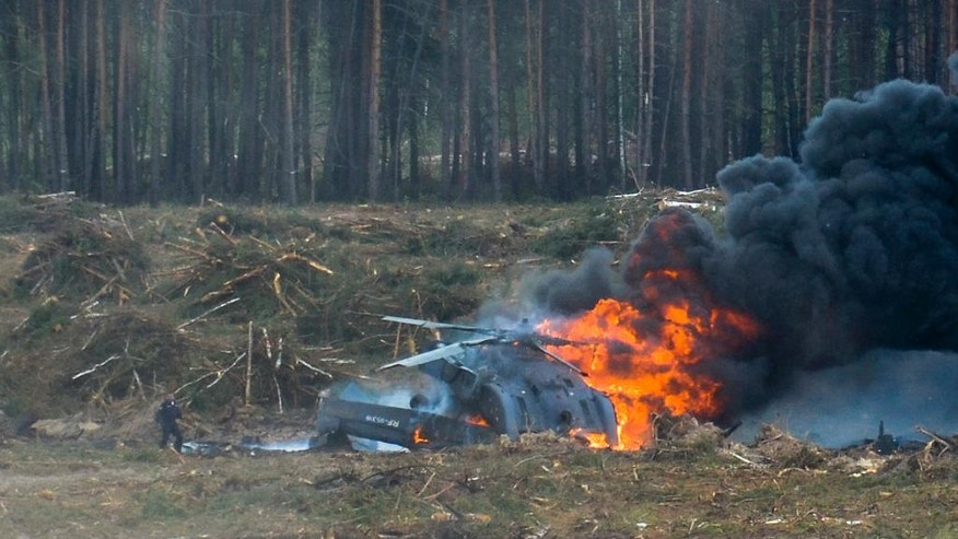 ALTERNATIVE CROP OF XAZ102 - A Russian military helicopter burns after crashing during an aerobatic display in Dubrovichi, Russia, Sunday, Aug. 2, 2015 , killing one of its crew members and injuring another. The Mi-28 helicopter gunship was part of a flight of helicopters performing aerobatics at the Dubrovichi firing range in Ryazan region, about 170 kilometers (105 miles) southeast of Moscow, when it crashed Sunday. (Anton Nasonov, RZN.info/Photo via AP)