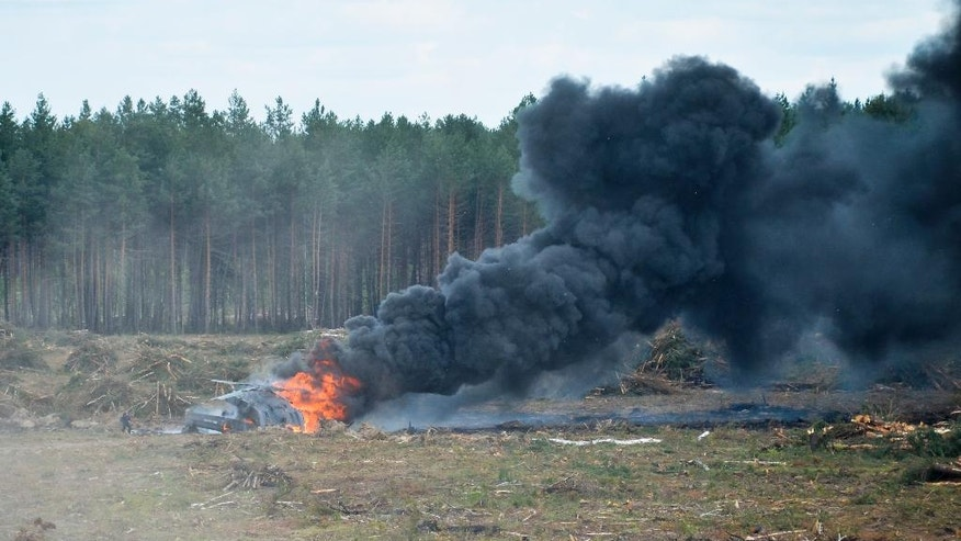 A Russian military helicopter burns after crashing during an aerobatic display in Dubrovichi, Russia, Sunday, Aug. 2, 2015 , killing one of its crew members and injuring another. The Mi-28 helicopter gunship was part of a flight of helicopters performing aerobatics at the Dubrovichi firing range in Ryazan region, about 170 kilometers (105 miles) southeast of Moscow, when it crashed Sunday. (Anton Nasonov, RZN.info/Photo via AP)