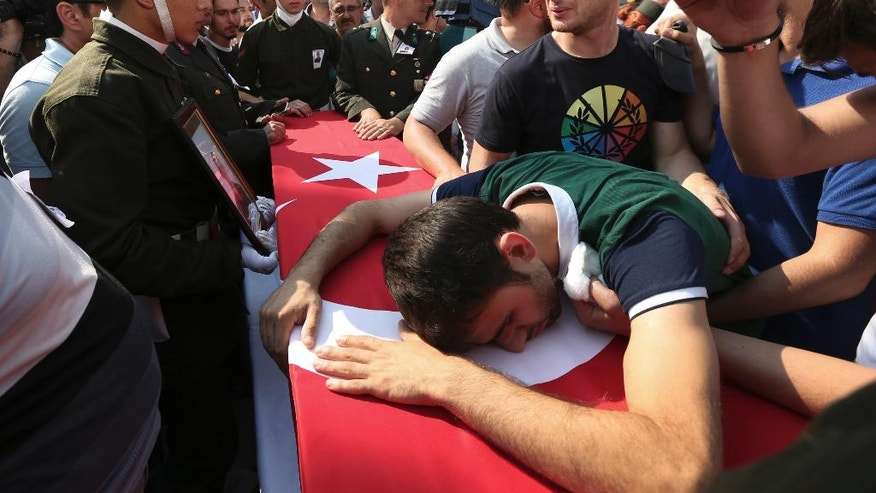 A relative cries over the Turkish flag-draped coffin of Turkish soldier Kagan Kandemir, during his funeral in the town of Civril, Turkey, Friday, July 31, 2015. Kandemir, was one of the three Turkish troops that were killed on July 30 when Kurdistan Workers' Party, or PKK militants opened fire on their convoy in the southeastern province of Sirnak, according to the army. (AP Photo/Depo Photos)  TURKEY OUT