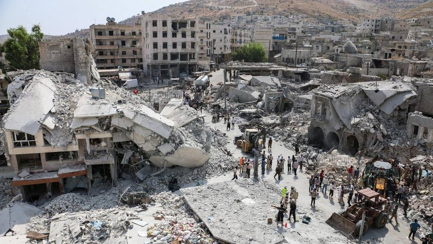 This photo provided by the Syrian anti-government activist group Ariha Today, which has been authenticated based on its contents and other AP reporting, shows the scene after a government  warplane crashed in the center of the town of Ariha, in the northwestern province of Idlib, Syria, Monday, Aug. 3, 2015. Air raids and the subsequent crash of a Syrian warplane in a residential area in the northwestern town of Ariha on Monday killed and wounded dozens of people, two activist groups said. (Ariha Today via AP)
