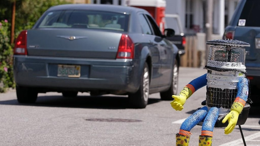 FILE- In this July 17, 2015, file photo, a car drives by HitchBOT, a hitchhiking robot in Marblehead, Mass. The Canadian researchers who created hitchBOT as a social experiment say someone in Philadelphia damaged the robot beyond repair on Saturday, Aug. 1, ending its brief American tour. The robot was trying to travel cross-country after successfully hitchhiking across Canada last year and parts of Europe. (AP Photo/Stephan Savoia, File)