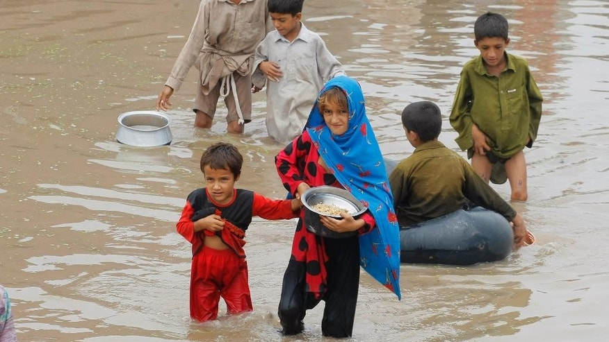 Pakistani flood victims wade through floodwater, carrying food for their family provided by volunteers in Peshawar, Pakistan, Monday, Aug. 3, 2015. Pakistani authorities said the death toll from flash floods triggered by seasonal monsoon rains in various parts of the country has risen to more than 100. Meanwhile, floodwater has inundated vast areas, leaving tens of thousands homeless. (AP Photo/Mohammad Sajjad)