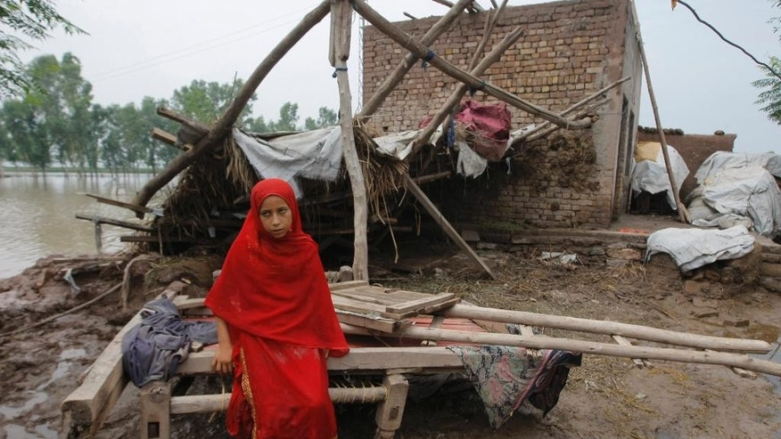 A Pakistani girl sits on remains of her house which is destroyed by floodwater in Peshawar, Pakistan, Monday, Aug. 3, 2015. Pakistani authorities said the death toll from flash floods triggered by seasonal monsoon rains in various parts of the country has risen to more than 100. Meanwhile, floodwater has inundated vast areas, leaving tens of thousands homeless. (AP Photo/Mohammad Sajjad)