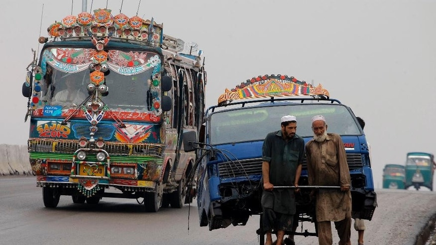 Pakistani laborers transport the front portion of a vehicle using a handcart at a road in Peshawar, Pakistan, Monday, Aug. 3, 2015. (AP Photo/Mohammad Sajjad)
