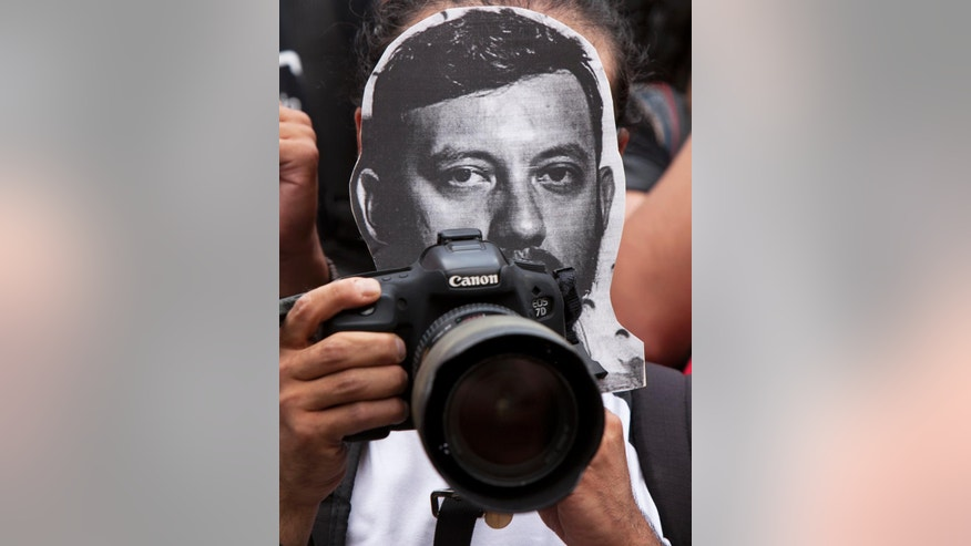 A photojournalist protests the murder of photojournalist Ruben Espinosa Becerril as he holds a printout of his photo, in Mexico City, Sunday, Aug. 2, 2015. Espinosa, 31, who worked for the investigative magazine Proceso and other media was found murdered along with 4 women, in an apartment in a middle-class neighborhood of Mexico City, where he had fled because of harassment in the state he covered. (AP Photo/Marco Ugarte)