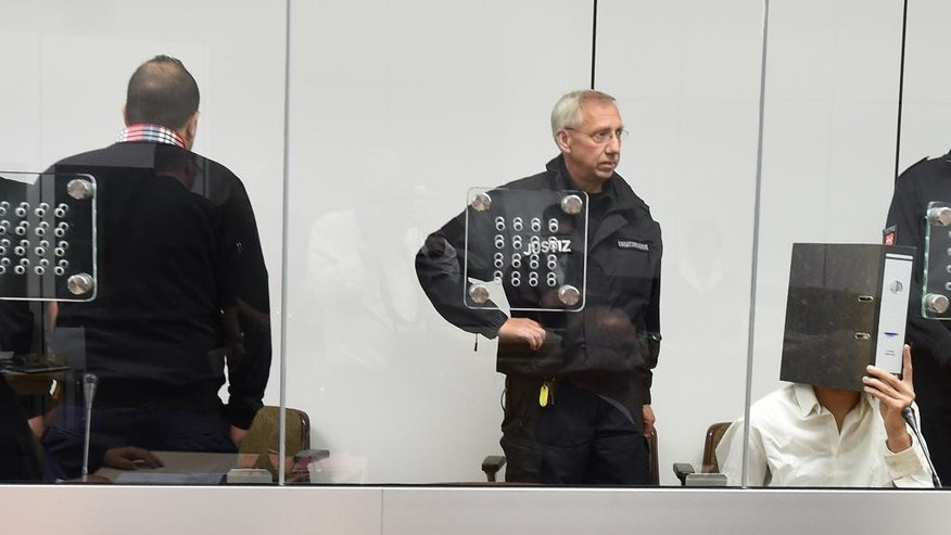 "Defendants Ebrahim H. B. ,26,  at left , back to camera, and  Ayoub B. right,  covered by a file folder,  wait  behind security glass at the  regional court  in Celle, Germany, Monday Aug. 3,  2015. The  26-year-old German ex-jihadist says he plans to reveal details about the inner workings of the Islamic State group ""so that the world knows the truth."" Ebrahim H. B. went on trial Monday alongside 27-year-old Ayoub B. charged with membership of a terrorist organization. The two German-Tunisian citizens, whose surnames weren't released due to German privacy rules, allegedly traveled to Syria last year to join IS.  (Holger Hollemann/Pool Photo via AP)"