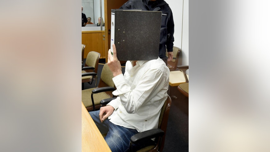 "Defendant  Ayoub B., 27,   covers his face as he sits  behind security glass at the  regional court in Celle, Germany, Monday Aug. 3, A  26-year-old German ex-jihadist says he plans to reveal details about the inner workings of the Islamic State group ""so that the world knows the truth."" Ebrahim H. B. went on trial Monday alongside 27-year-old Ayoub B. charged with membership of a terrorist organization. The two German-Tunisian citizens, whose surnames weren't released due to German privacy rules, allegedly traveled to Syria last year to join IS.  (Holger Hollemann/Pool Photo via AP)"