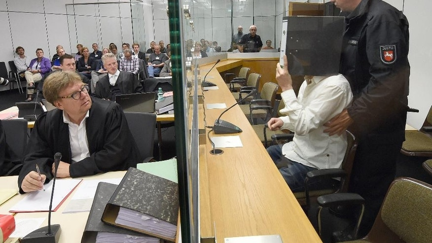 "Defendant  Ayoub B. 27,  right,  covers his face as he sits  behind security glass at the regional court  in Celle, Germany, Monday Aug. 3,  2015.  At left one of his lawyers, Dirk Schoenian. A  26-year-old German ex-jihadist says he plans to reveal details about the inner workings of the Islamic State group ""so that the world knows the truth."" Ebrahim H. B. went on trial Monday alongside 27-year-old Ayoub B. charged with membership of a terrorist organization. The two German-Tunisian citizens, whose surnames weren't released due to German privacy rules, allegedly traveled to Syria last year to join IS.  (Holger Hollemann/Pool Photo via AP)"