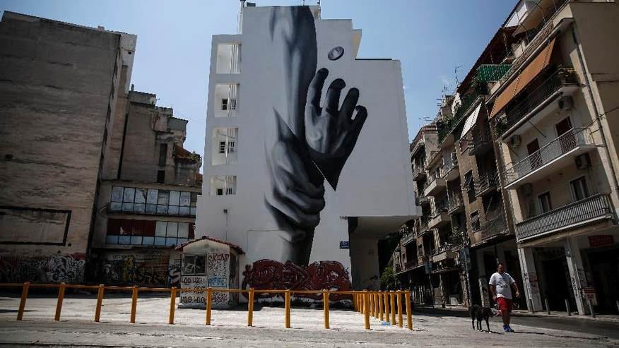 A man walks with his dog past a mural at a central neighborhood in Athens, Greece, on Sunday, Aug. 2, 2015. In Athens, the heads of the EU-IMF audit mission met with the Greek ministers of finance and economy with the talks focusing on bank recapitalisation, privatisations and fiscal targets, the finance ministry said.  (AP Photo/Yorgos Karahalis)