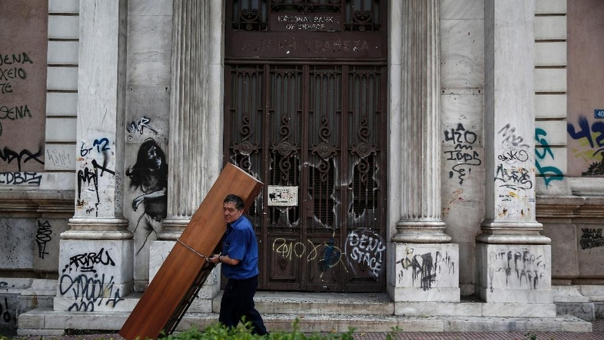 A man carries a closet past an abandoned branch of the National bank in Athens, Greece, on Sunday, Aug. 2, 2015. In Athens, the heads of the EU-IMF audit mission met with the Greek ministers of finance and economy with the talks focusing on bank recapitalisation, privatisations and fiscal targets, the finance ministry said.  (AP Photo/Yorgos Karahalis)