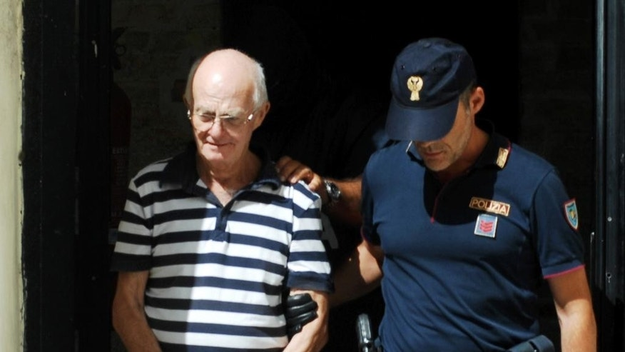 An Italian police officer takes in custody Ugo Di Leonardo, left, one of the 11 men suspected of helping No. 1 Cosa Nostra fugitive Matteo Messina Denaro, in Palermo, Italy, Monday, Aug. 3, 2015. Italian investigators say they've discovered how the No. 1 Cosa Nostra fugitive communicates with henchmen using written messages buried in dirt or hidden under boulders on Sicilian sheep ranches: in pre-dawn raids Monday in western Sicily, police arrested 11 men suspected of helping Matteo Messina Denaro stay in command despite being on the run since 1993. (AP Photo/Alessandro Fucarini)