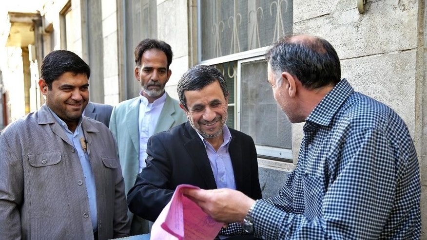 Former Iranian President Mahmoud Ahmadinejad, center, talks with a man before receiving his petition for help outside his house in northeastern Tehran, Iran, Monday, Aug. 3, 2015. Ahmadinejad received petitions for help there to pass on to authorities. He has launched a political campaign ahead of parliamentary elections in February 2016 in what could prove a challenge to the moderates behind a landmark nuclear agreement reached last month. (AP Photo/Ebrahim Noroozi)